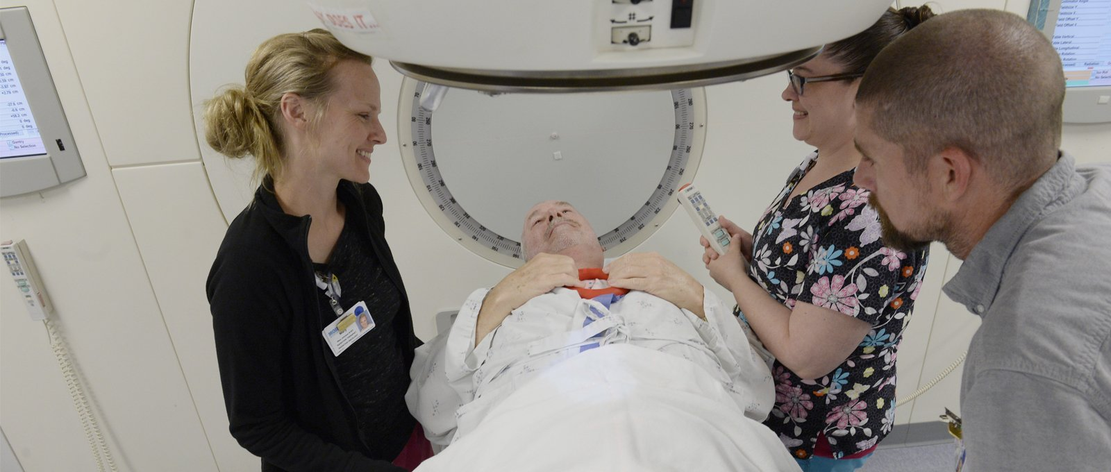 cancer patient getting a CT scan with friendly staff helping