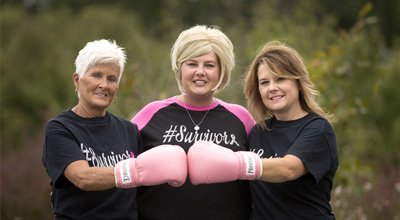Three women wearing breast cancer survivors shirts, wearing pink boxing gloves